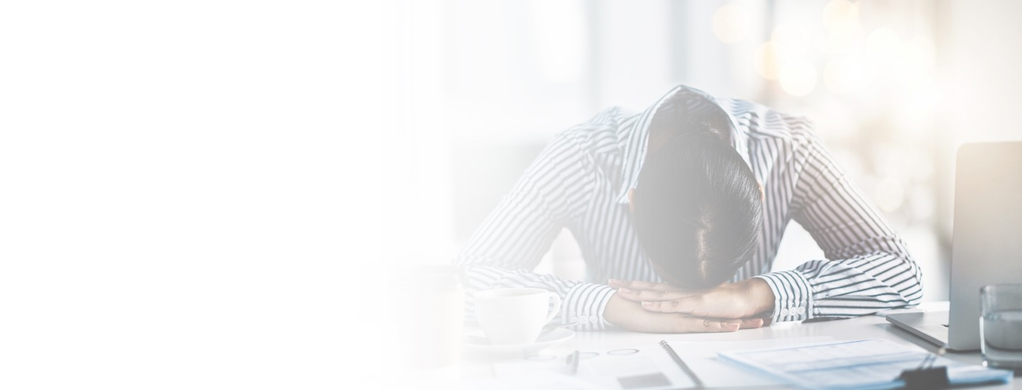 Cropped 2880x1100 left white gradient of a young businesswoman lying with her head down on a desk in an office