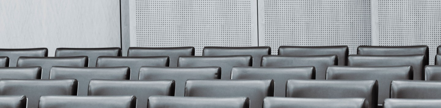2880x1100 of empty seats in a modern courtroom. Desaturated, Toned.