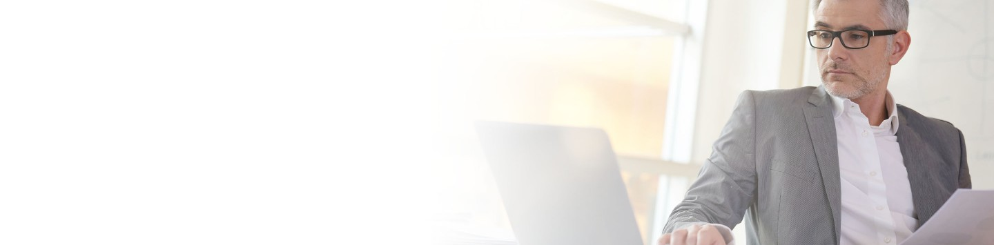 2880x1100 flipped horizontal left white gradient of a businessman in office working on laptop