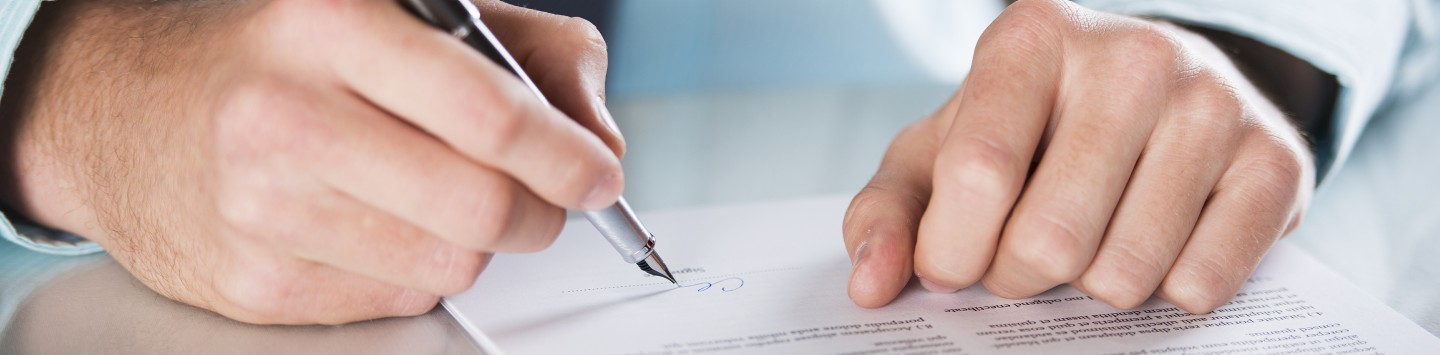 2880x1100 of a businessman's hands signing a contract on a table