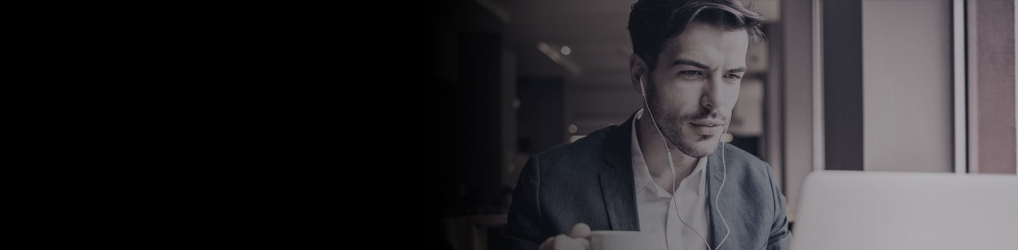 2880x1100 left black gradient of a smiling man with headphones working on a laptop and drinking coffee