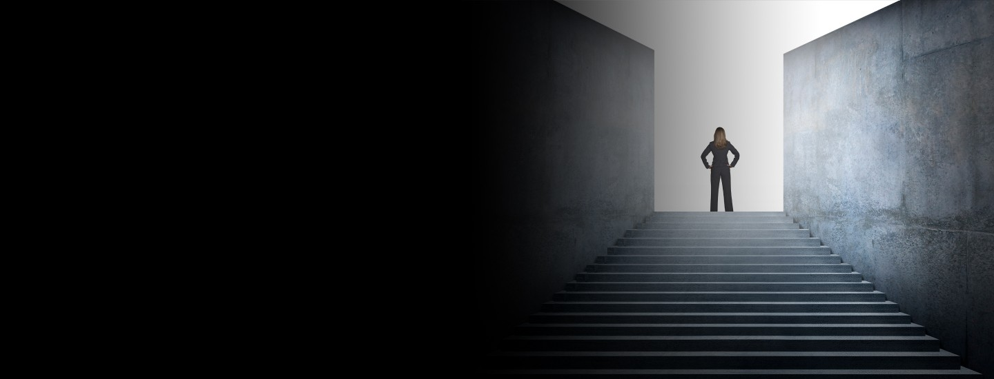 Cropped 2880x1100 left black gradient a businesswoman who has reached the top of the stairs looks out into the distance as she looks for her next challenge.