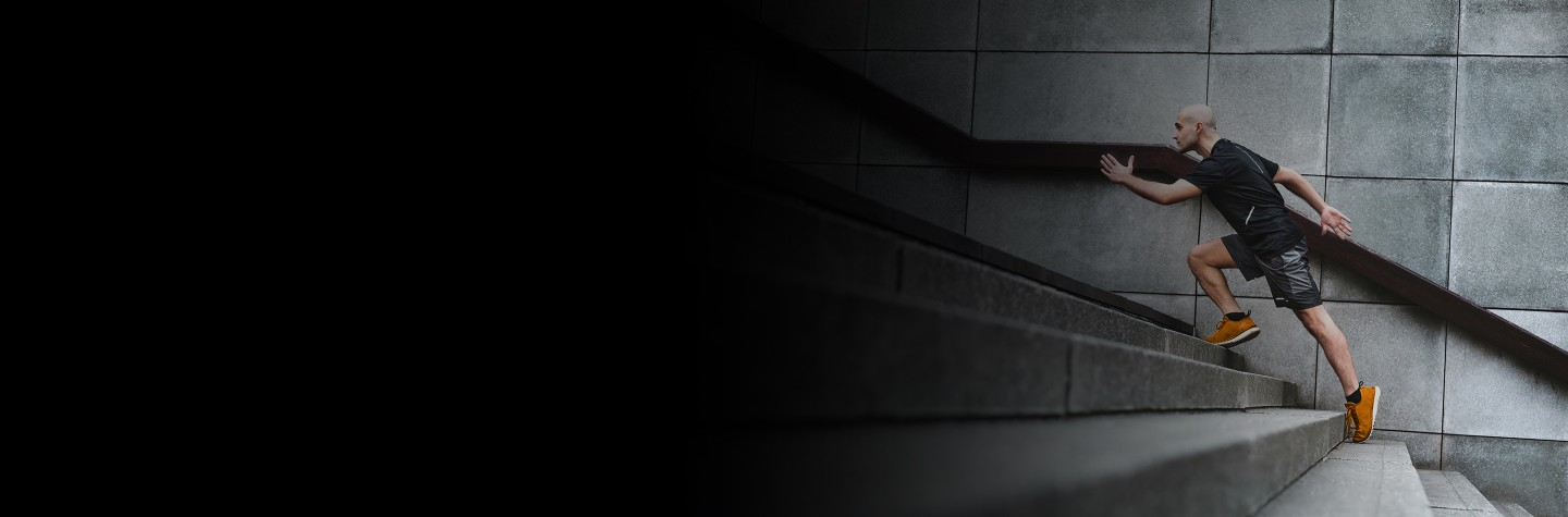 Cropped 2880x1100 left black gradient of Focussed runner man jogging on stairs